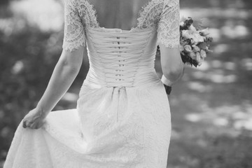 Black and white image of beautiful caucasian bride in wedding dress moving and holding a bouquet in her hands.