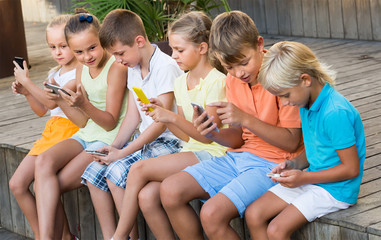 Group of smiling kids playing with mobile phones outdoors