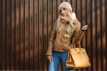 Attractive girl in wool hat leather jacket with beige bag