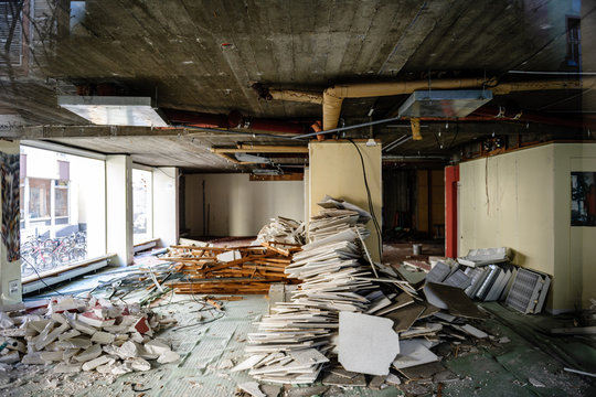 Horizontal view of abandoned interior of a business store market with lots of damaged lamps, walls