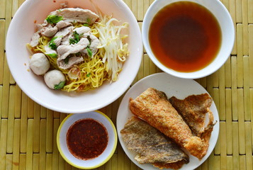 Chinese egg noodle topping pork ball and crispy fish skin with soup