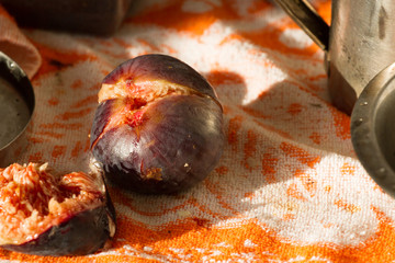 Ripe figs isolated lying on orange towel. Violet fruits of ficus carica