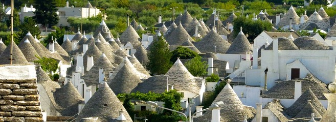 Trulli (plural of trullo) in Alberobello, Italy. View over unusual stone structures with conical rooftops, specific to Itria Valley in Apulia (Puglia).