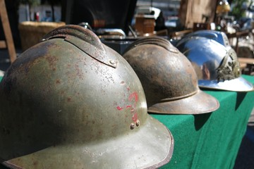 Antique military army helmets at flea market street market in Ostuni, Italy