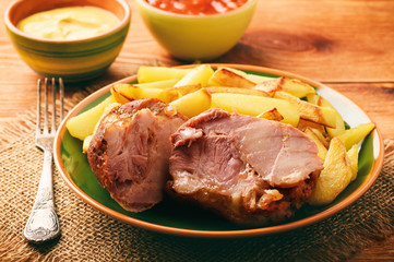 Baked pork knuckle with roasted potatoes.
