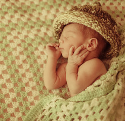 little wonderful baby  in a big hat lying in bed