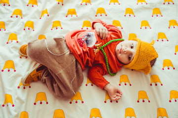 funny little  boy in yellow hat lying in bed