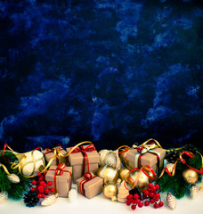 Christmas or New Year background: fur-tree, branches, gifts, colored glass balls, decoration and cones on a dark background