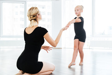 Ballet instructor directing little cute ballerina during dance practice