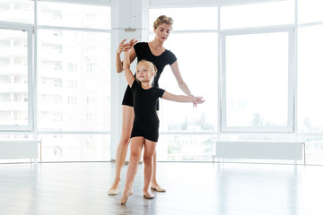 Little ballerina and teacher dancing in ballet school