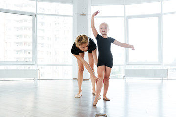 Graceful little ballerina and her teacher dancing in ballet school