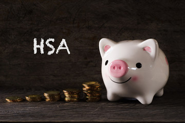 "HSA"" words Piggy bank and stack of golden money increased with wooden background - saving, finance and business concept"