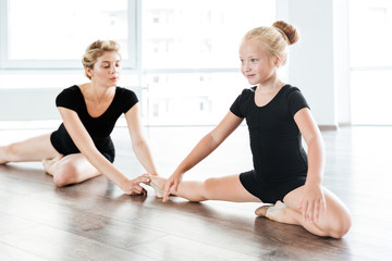 Happy little girl ballerina sitting and stretching legs with teacher