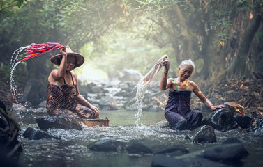Asian old women washing clothes at the creek