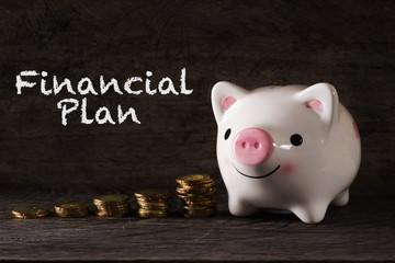 """Financial Plan"" words with Piggy bank and stack of golden money increased with wooden background - saving, finance and business concept"