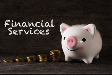 """Financial Services"" words with Piggy bank and stack of golden money increased with wooden background - saving, finance and business concept"