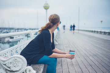 Woman with cup on the pier