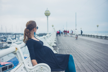 Pregnant woman on bench by the pier