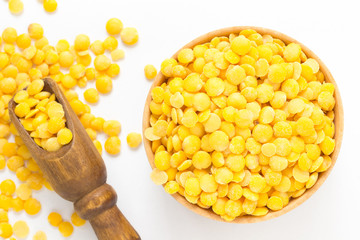 Yellow lentils in a wooden bowl. Wooden scoop