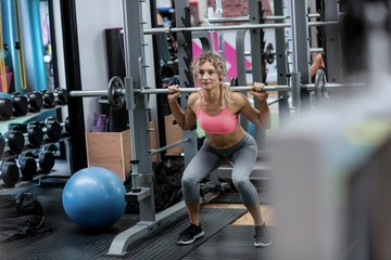 Beautiful woman working out with barbell