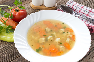 Soup with meatballs and vegetables in plate