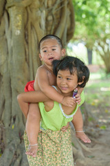 little asian boy sit on young girl's back ,they dress in Thai lo