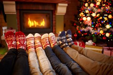 Feet in wool socks near fireplace in Christmas time.