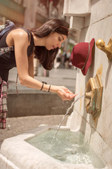Woman drinking water at the public street fountain