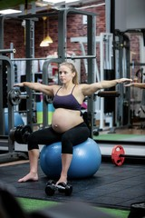 Pregnant woman preforming stretching exercise on fitness ball
