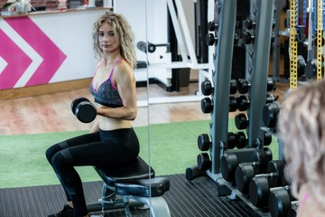 Young woman lifting dumbbells in gym