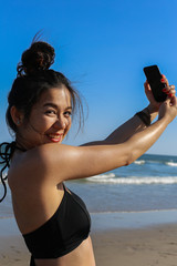 Young woman is take selfie by her cellphone on the beach