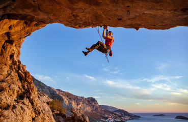 Male climber on challenging route in cave against beautiful coastal view