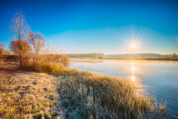 Sun Rises Over River. Autumn Frost Frozen River Covered With Thin Ice.