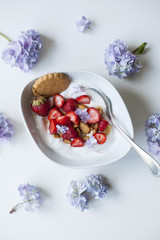 Coconut yogurt with strawberries and crushed coconut cookies