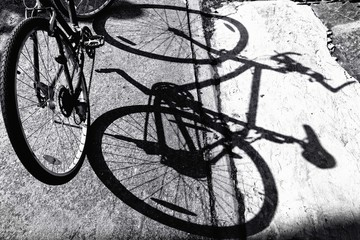 Black and white a bicycle against shadow