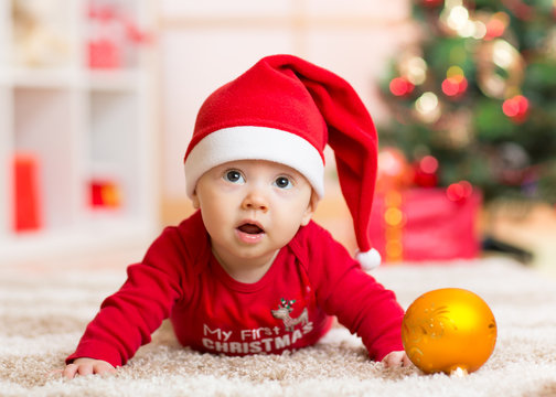 Funny baby lying on tummy wearing Santa hat and suit in front of Christmas tree
