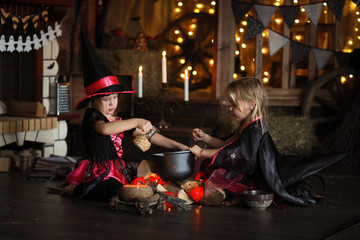 Two little Halloween  witches reading conjure above pot   childh