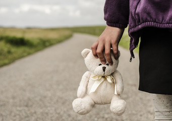 Refugee child goes on the road with her teddy bear