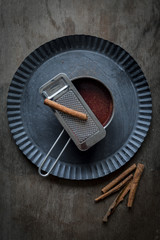 Chocolate sauce in small pot on rustic tin plate with freshly gr