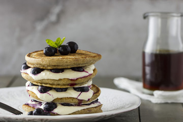 Pancake Stack with Yoghurt, Cream, Blueberries and Maple Syrup.