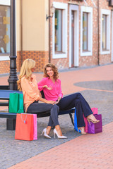 girls sit on a bench after shopping,holding shopping bags