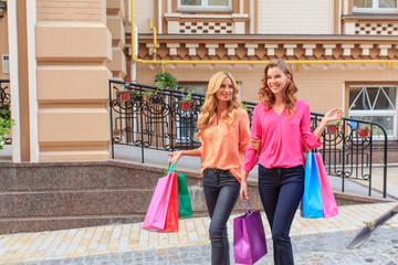 girls walking after shopping, holding shopping bags