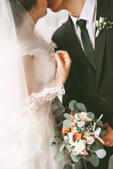 Bride and groom kissing and holding a wedding bouquet