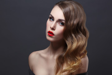 Fashion beauty portrait of gorgeous girl with curls and red lipstick in the style of Hollywood on a black background