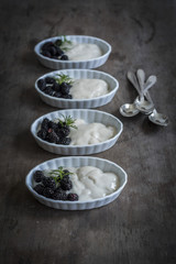 Mulberries and vanilla cream in china dishes on wooden backgroun