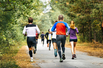 Fototapete - group of runners running down road in autumn Park with fallen yellow leaves. competition marathon