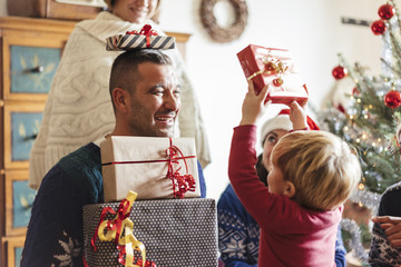 family at home sharing presents for christmas