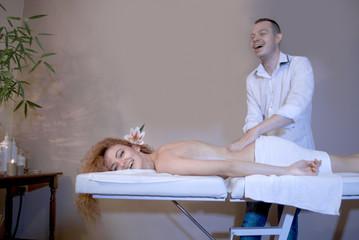 Man massaging beautiful women in massage studio