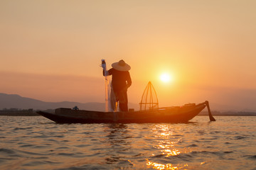 Silhouettes of the traditional stilt fishermen at sunset.