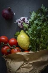 Vegetables in paper bag fresh from the market on slate backgroun